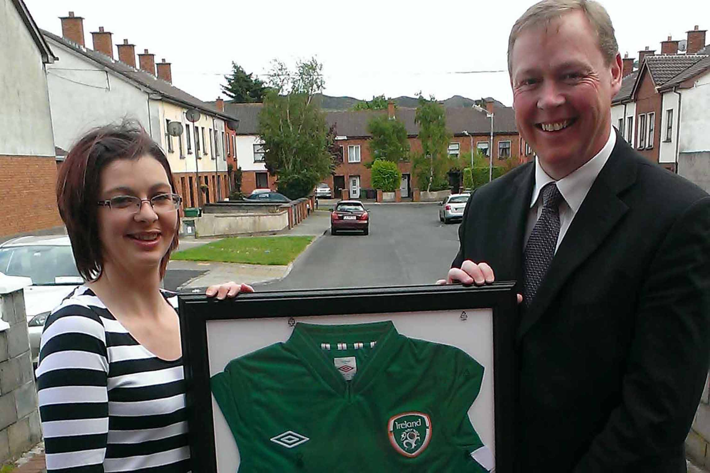 Danielle O' Brien with David Grant and the signed Irish soccer jersey which David donated to HeadsUp