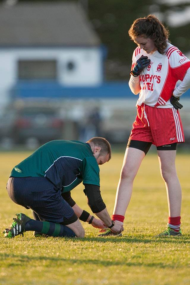 Ref Anthony Nolan helps Tinahely midfielder Aoife Gorman